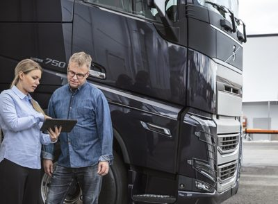 A man and woman stand in front of a truck looking at a tablet