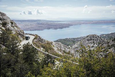 Un camión circula por una sinuosa carretera de la costa